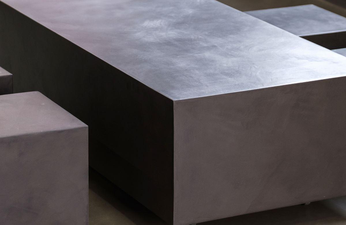 detalle de mesa baja de microcemento con taburetes cubos