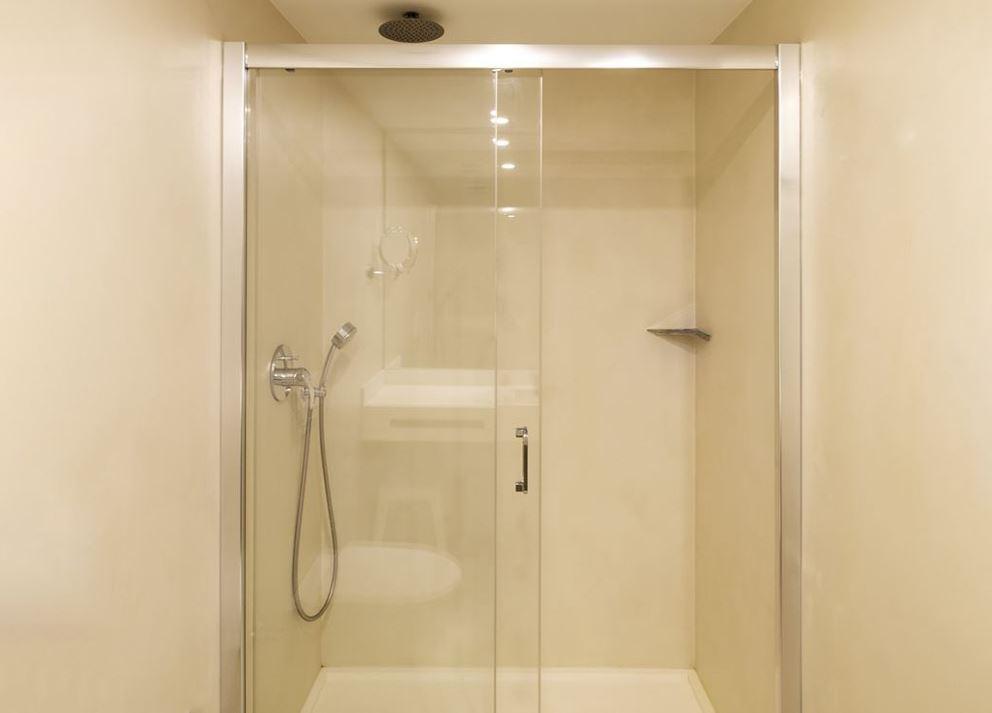 ducha con paredes de microcemento en baño de hotel