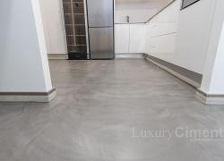suelo de cocina revestido de microcemento gris a juego con muebles bancos