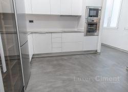 suelo de microcemento gris en una cocina a juego con muebles bancos